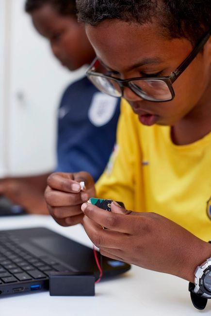 一位年輕男孩正在操作 micro:bit