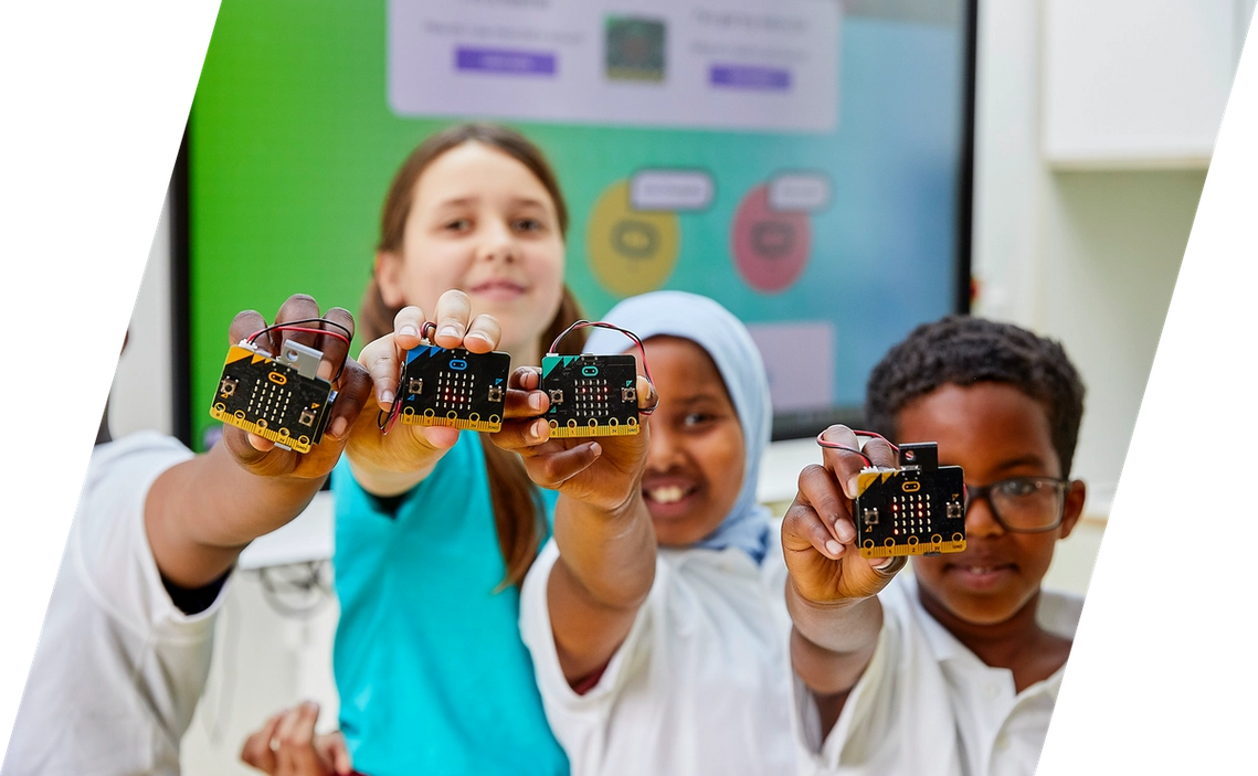 children in class smiling and holding micro:bits