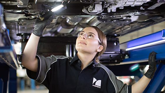 female motorserve mechanic inspecting car in workshop
