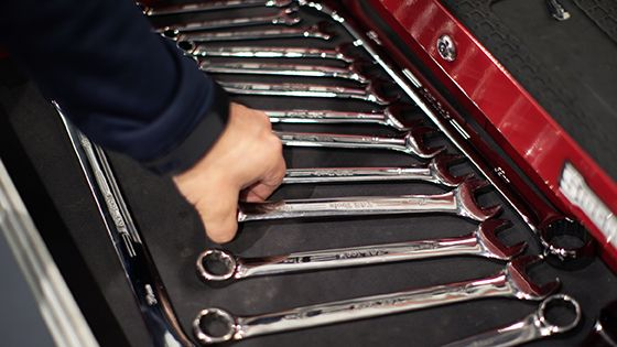 hand reaching for wrenches