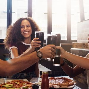 Multi-ethnic group of people toasting cold drinks with pizza on table at restaurant.