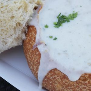 Close-up of clam chowder served in sourdough bread bowl and garnished with herbs, a delicious traditional American street food found at vendors or restaurants in San Francisco, California, US