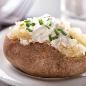 A delicious oven baked potato with sour cream and chives.