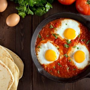 Shakshuka with eggs, tomato, and parsley in a cast iron pan.