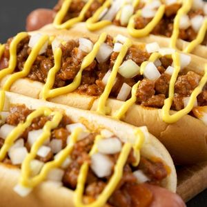 Homemade Detroit style chili dog on a rustic wooden board on a black surface, side view. Close-up.