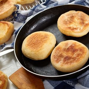 cooking breakfast - baking english muffins on a skillet and are chilling on a grid on wooden table with kitchen towel, fresh butter and knife, view from above, close-up
