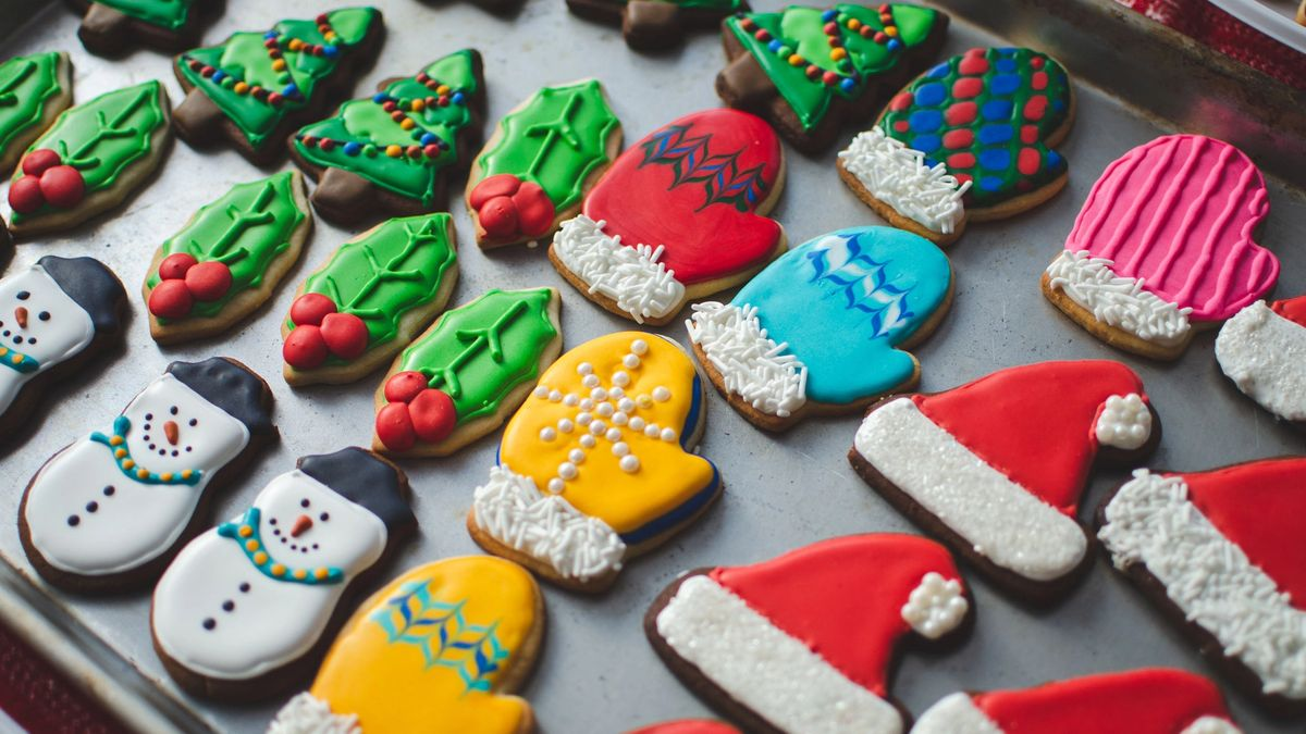 A variety of beautifully decorated Christmas sugar and gingerbread cookies on a baking sheet