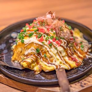 Japanese okonomiyaki covered with katsuobushi leek mayonnaise and bulldog sauce served on a hot plate with spatulas. Katsuobushi beef bulldog served on a plate covered with cheese sauce and spicy sauce with leek, okonomiyaki sauce, served with roasted vegetables and katsuob sushi. Taken in japan. Japanese cuisine and diet. Tasty cooked beef bulldog covered with mayonnaise sauce served with katsuobushi, leek and avocado. Japanese culture and cooking food okonomiyaki.