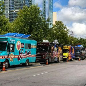 Dallas, TX, USA - October 6, 2018:  Several colorful food trucks are parked all in a row on a street beside a public park on a Saturday on October 6, 2018 in Dallas, TX.