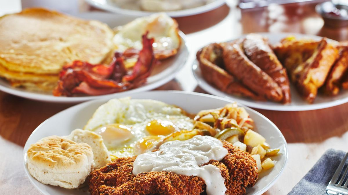 chicken fried steak covered in gravy with sunny side up eggs and breakfast foods