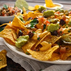 Mexican nachos tortilla chips with olives, jalapeno, guacamole, tomatoes salsa, cheese dipand beer.
