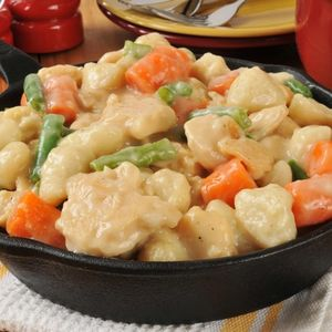 Hearty chicken and dumplings in a cast iron skillet on a rustic wooden table