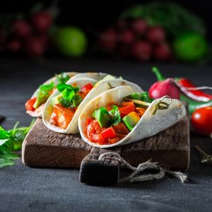 Tacos with spicy sauce and coriander on concrete table