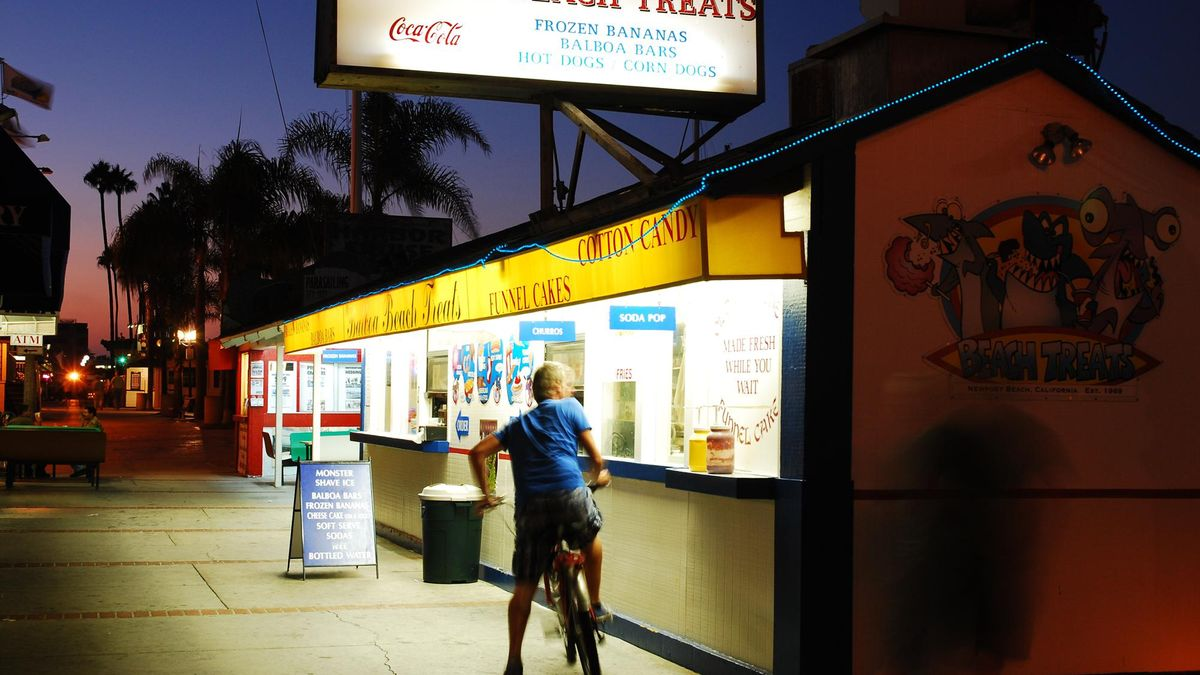 A teenage boy bikes up to an ice cream stand in Newport Beach California at dusk
