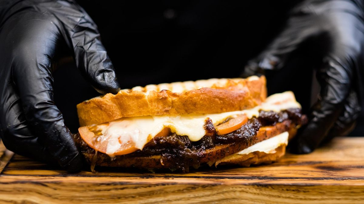 Professional catering. Chef hands serving smoked turkey breast sandwich on wooden board.