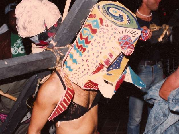 Border Arts Workshop performer wearing ladies lingerie, covered in a mask, and carrying a crucifix.