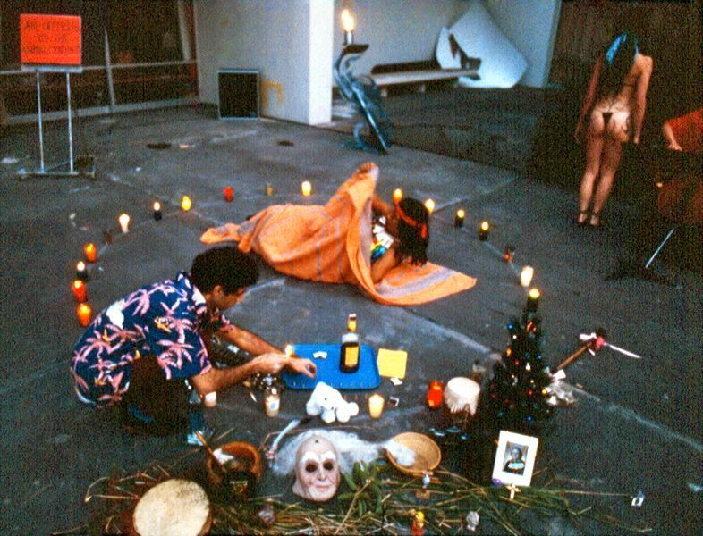 Guillermo Gómez-Peña crouching down in a ritual scene including candles, masks, photographs, and two other performers.