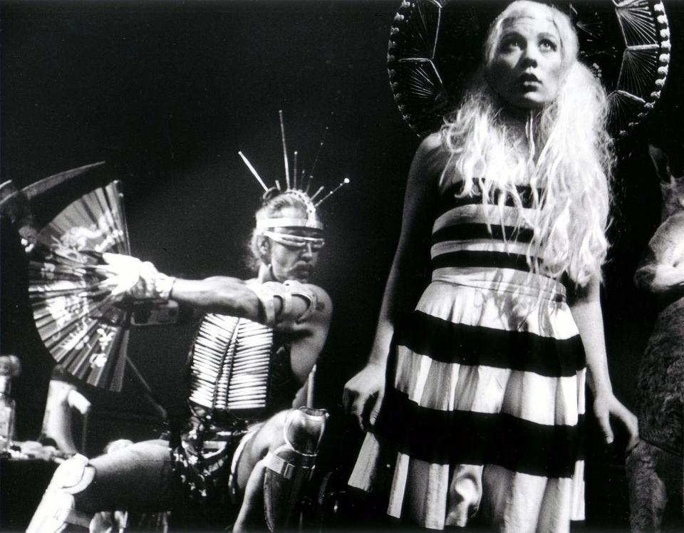 Guillermo Gómez-Peña seated with cyber-ethnic costumery and sunglasses next to a standing woman looking upwards with pale hair, sombrero, and a black and white dress.