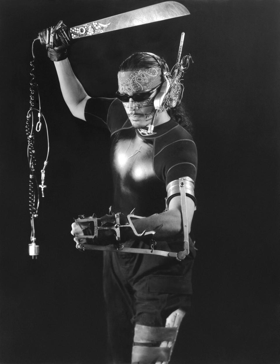 Roberto Sifuentes in latino cyborg garb. Machete in right hand, sunglasses, metallic prosthesis surrounding his left arm.