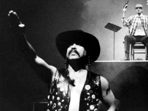 Guillermo Gómez-Peña in a black leather vest and hat with right armed salute. Latino gang member on stage in the background with a woman in a dark dress nearby,