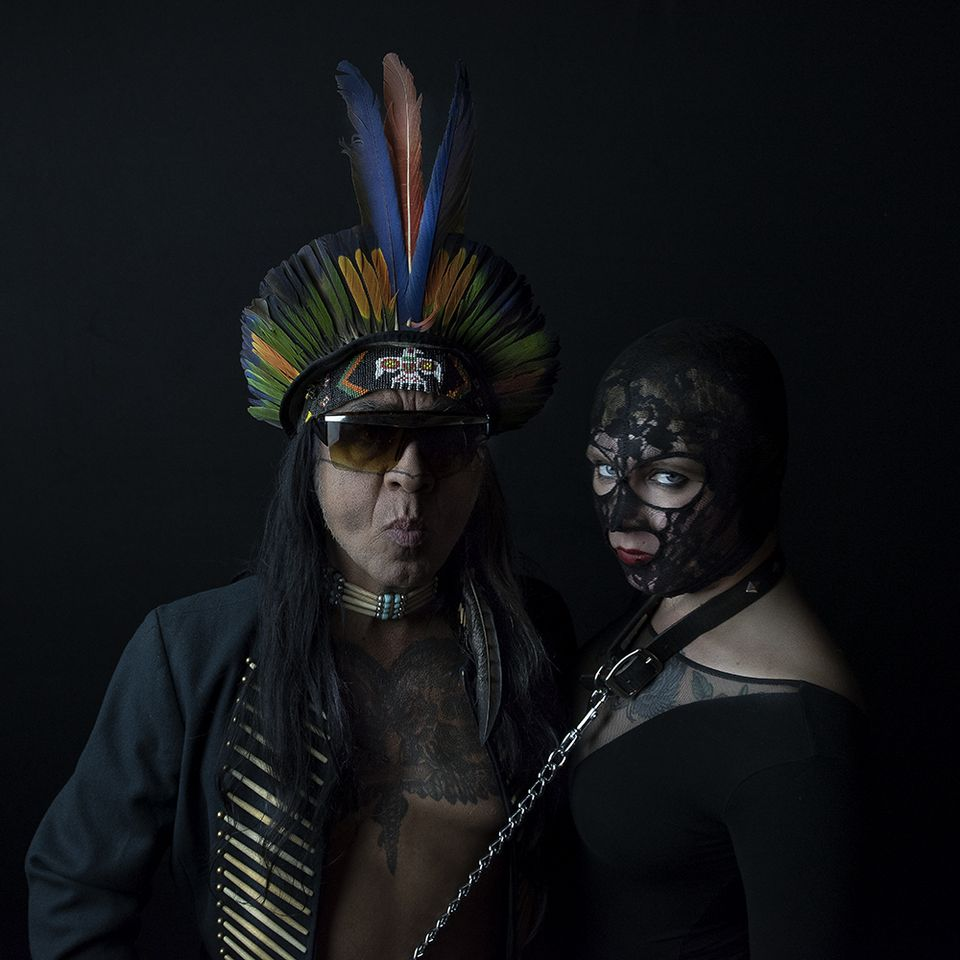 Guillermo Gómez-Peña in a black jacket with exposed bare tattooed chest. Wearing sunglasses and a feather headdress.