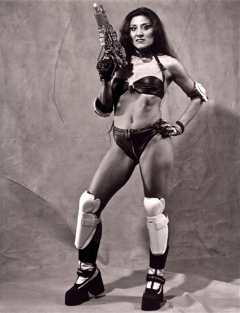 Latina woman in a bikini with a toy gun, knee and shoulder pads, high platform shoes.