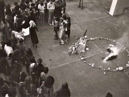 A crowd of people surround a circle of candles and ritual objects on a concrete floor.