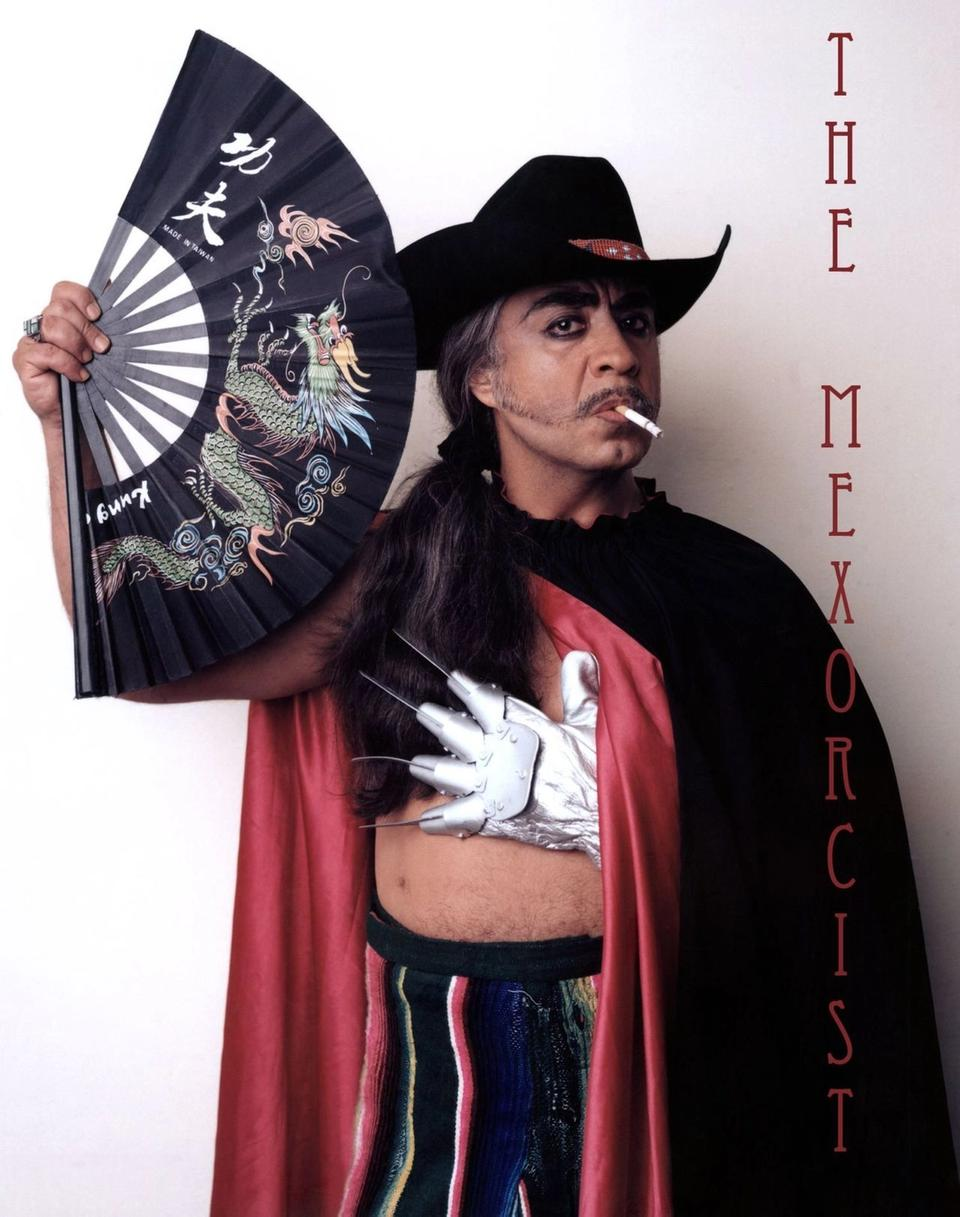 Gómez-Peña in black cape, black cowboy hat, holding an Asian fan in one hand and with a white Freddy Krueger style knife-glove in the other.