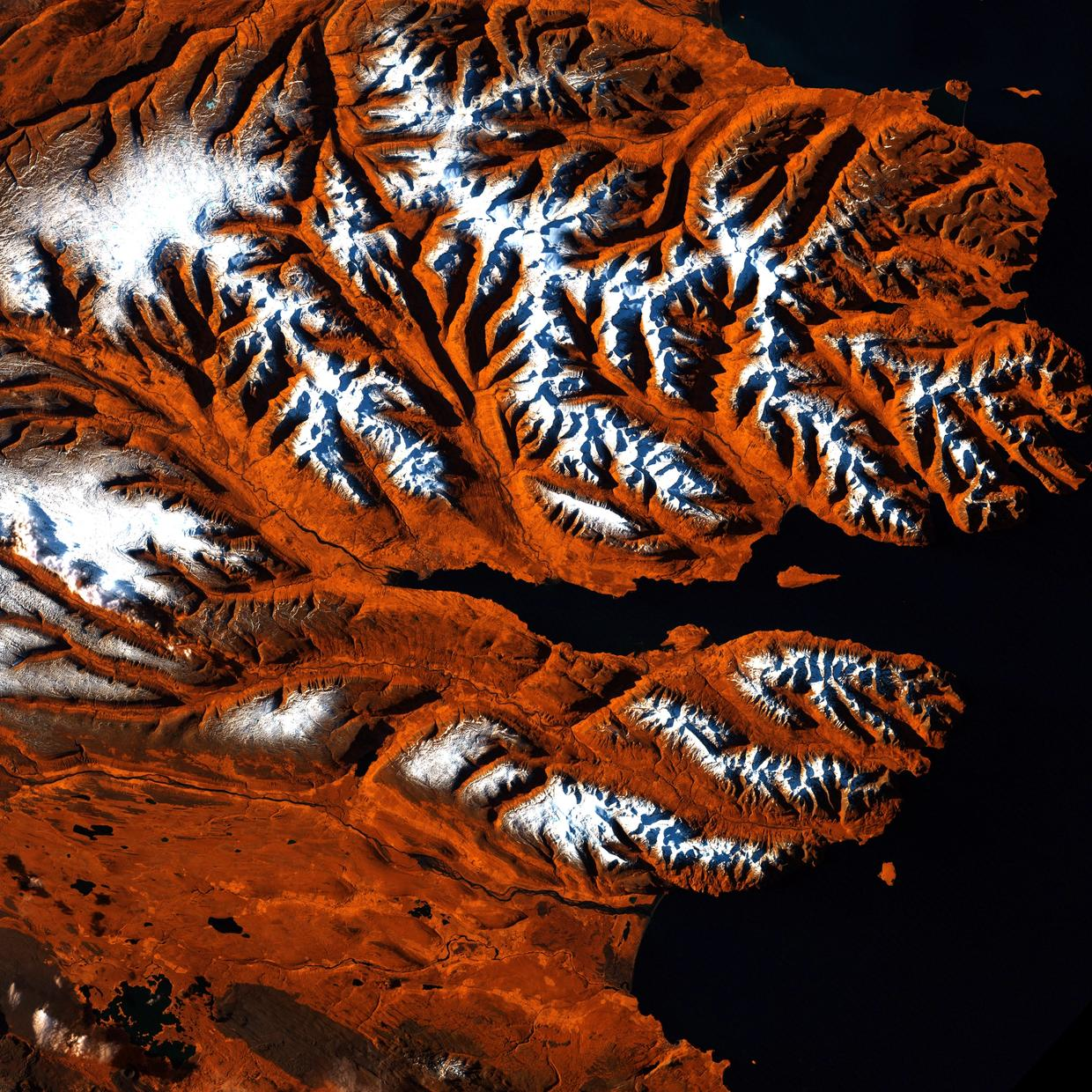 This stretch of Iceland's northern coast resembles a tiger's head complete with stripes of orange, black, and white. The tiger's mouth is the great Eyjafjorour, a deep fjord that juts into the mainland between steep mountains. The name means