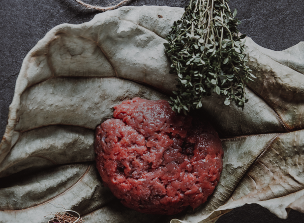 Wild venison mince displayed on large dried leaves
