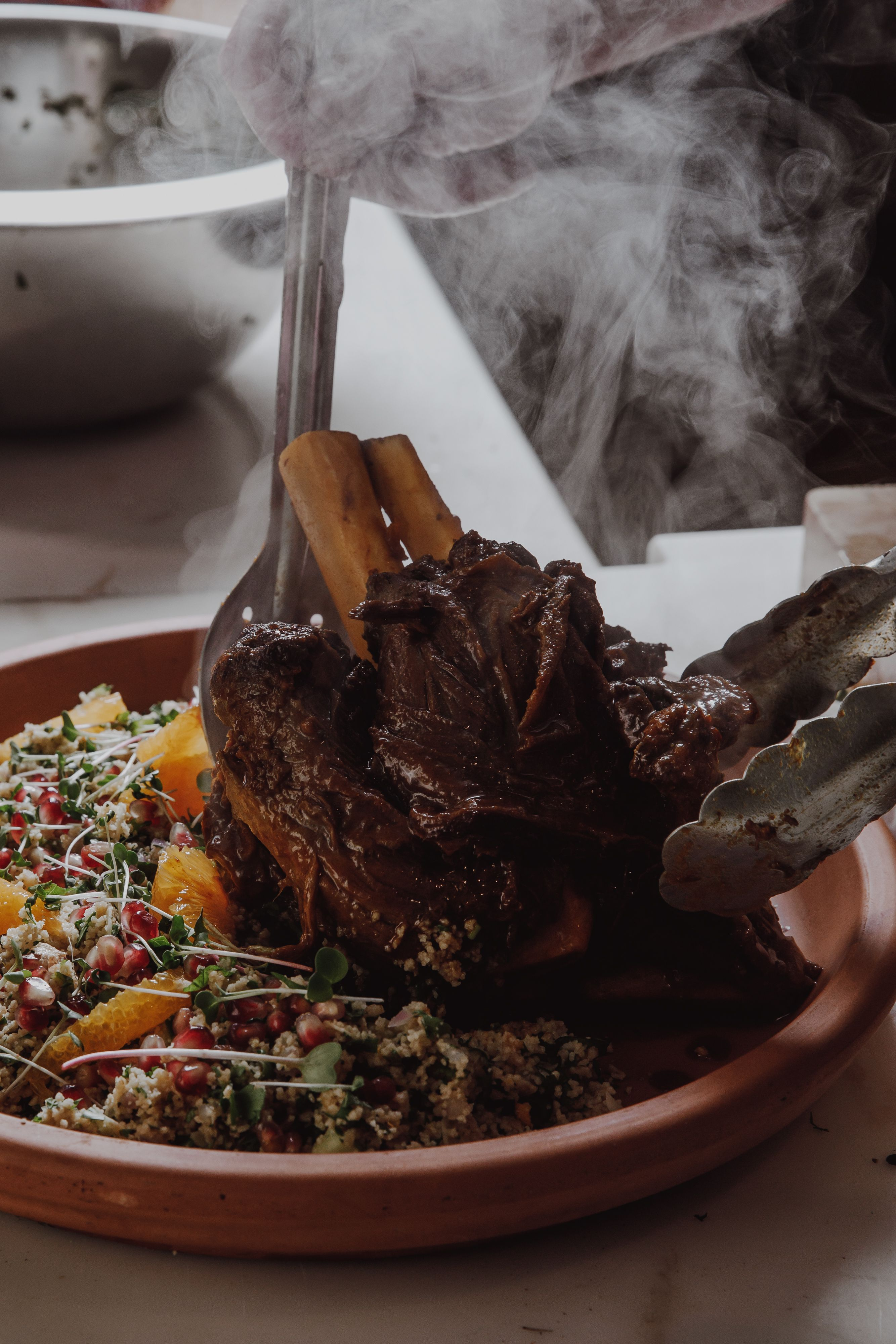 Venison Tagine being served with Cous cous on plate