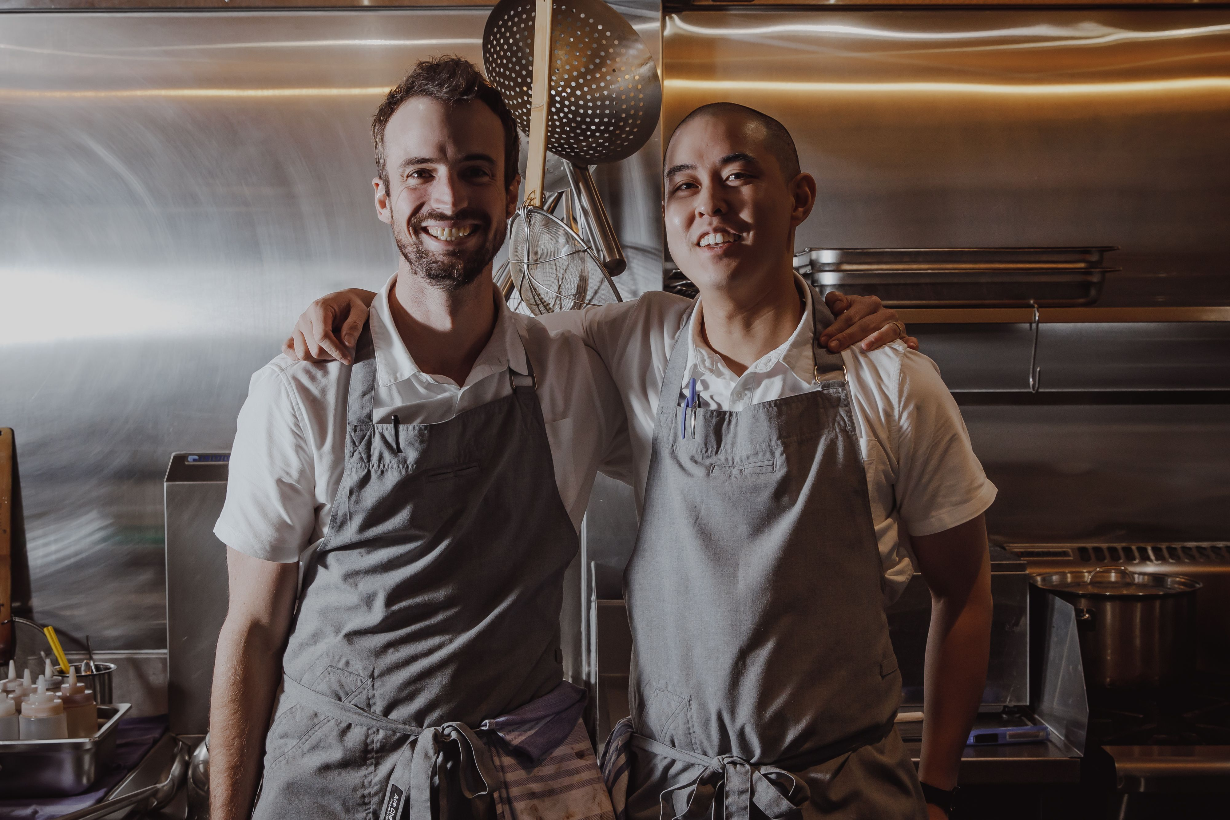 Chefs Ned Trumble & Keat Lee of Lagoon Dining standing in kitchen smiling