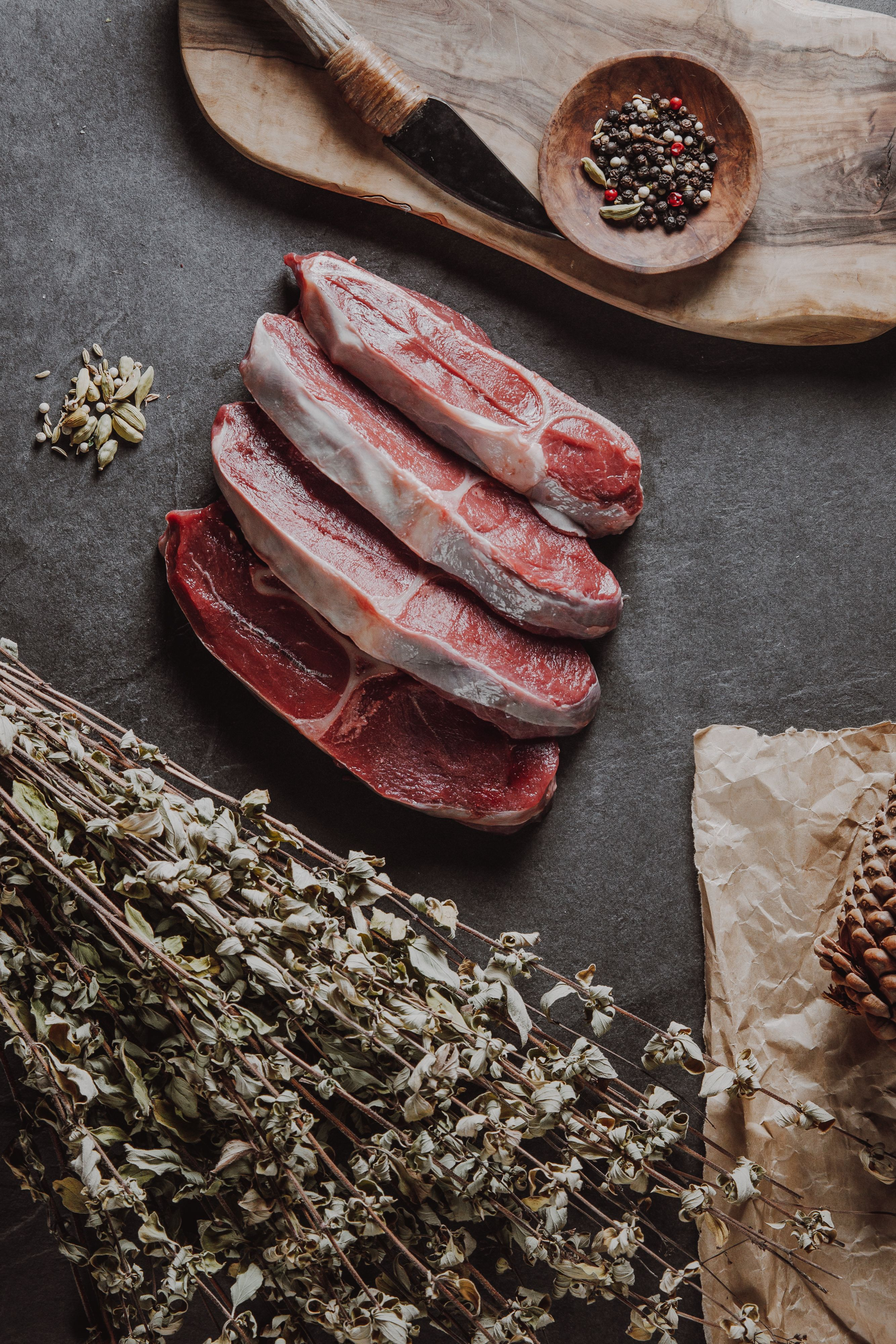 Wild venison shoulder blade chops on kitchen bench surrounded by herbs