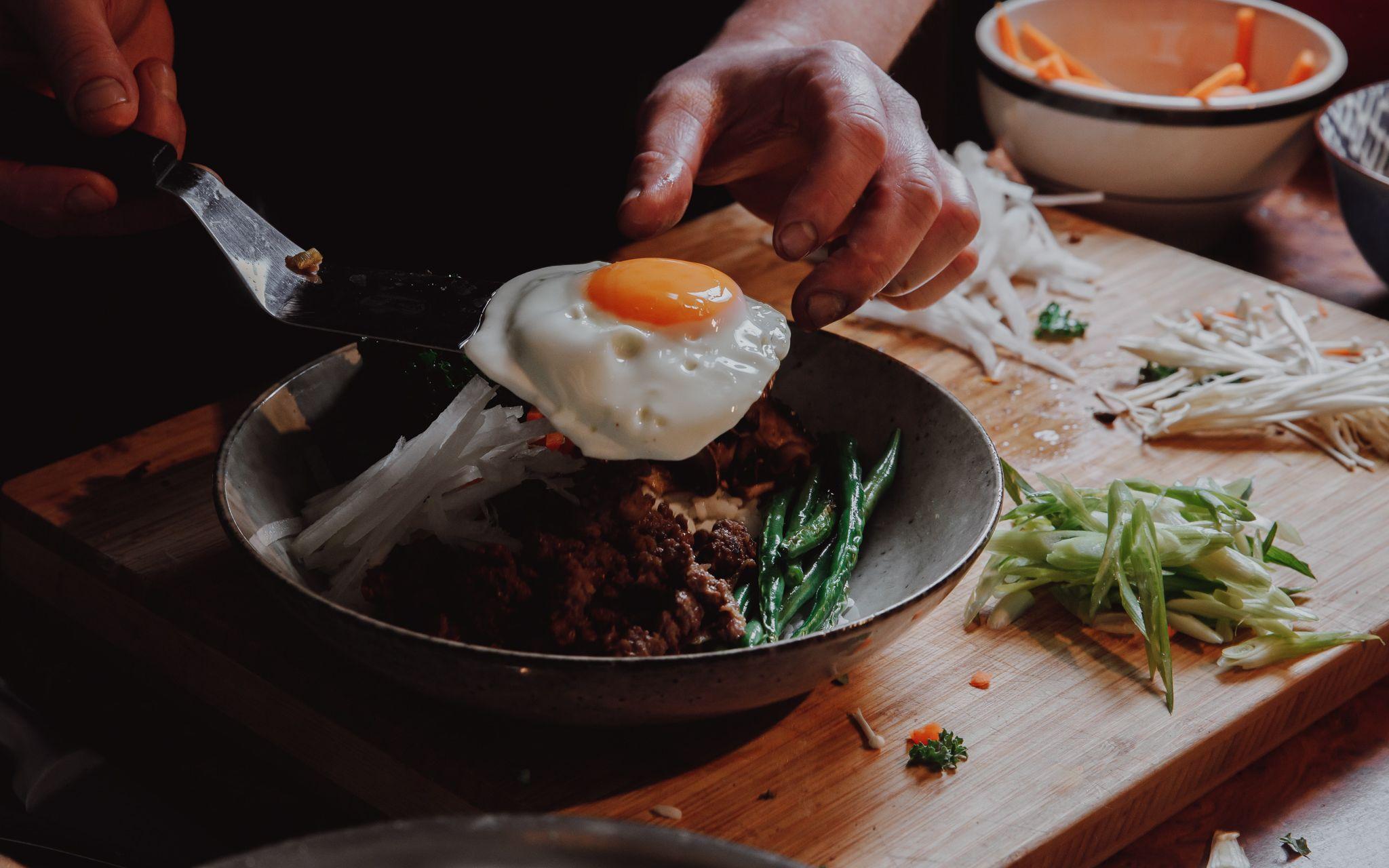Venison Bi bim bap being plated with a fried egg