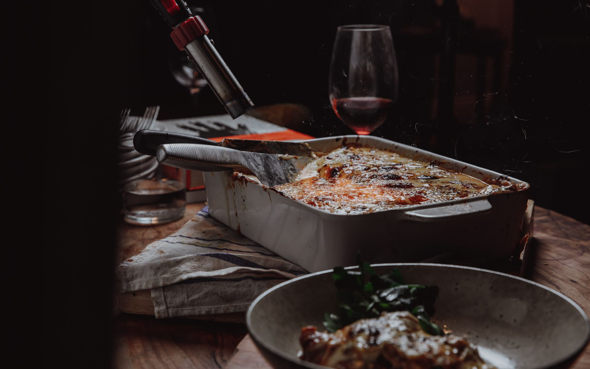 Venison Lasagne ready to be served, alongside a glass of red wine