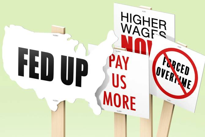 """Picket signs that read """"Fed up"""" """"Pay us more"""" """"Higher wages now""""  and crossed out """"forced overtime"""""""
