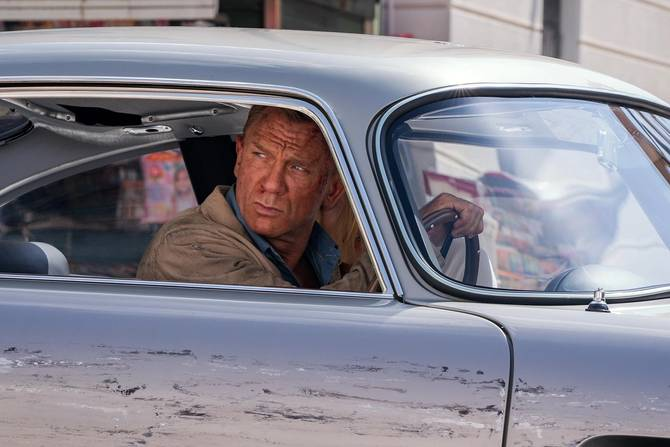 Daniel Craig as James Bond in 'No Time To Die' in a deeply scratched car.