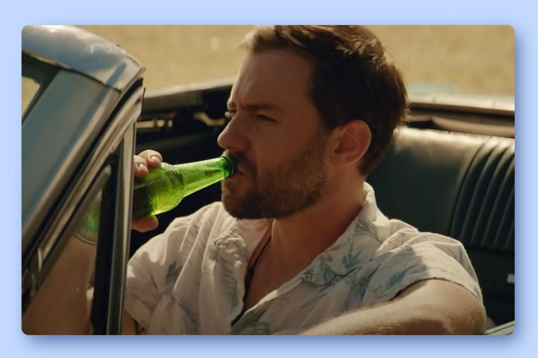 A man sitting in a car drinking Heineken 0.0