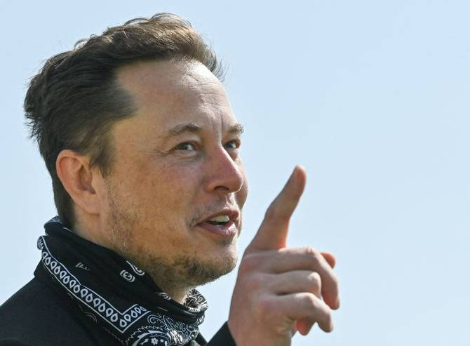 Elon Musk gestures during a visit at the Tesla Gigafactory plant under construction