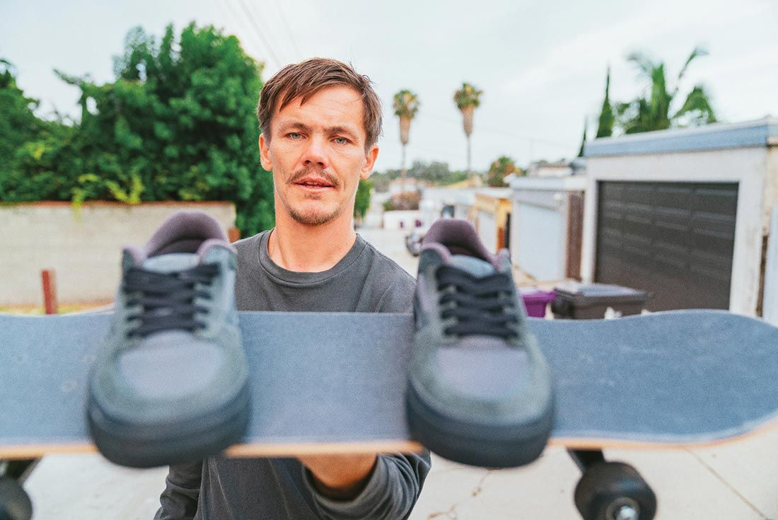 Geoff Rowley Holding Skate Board And Shoes