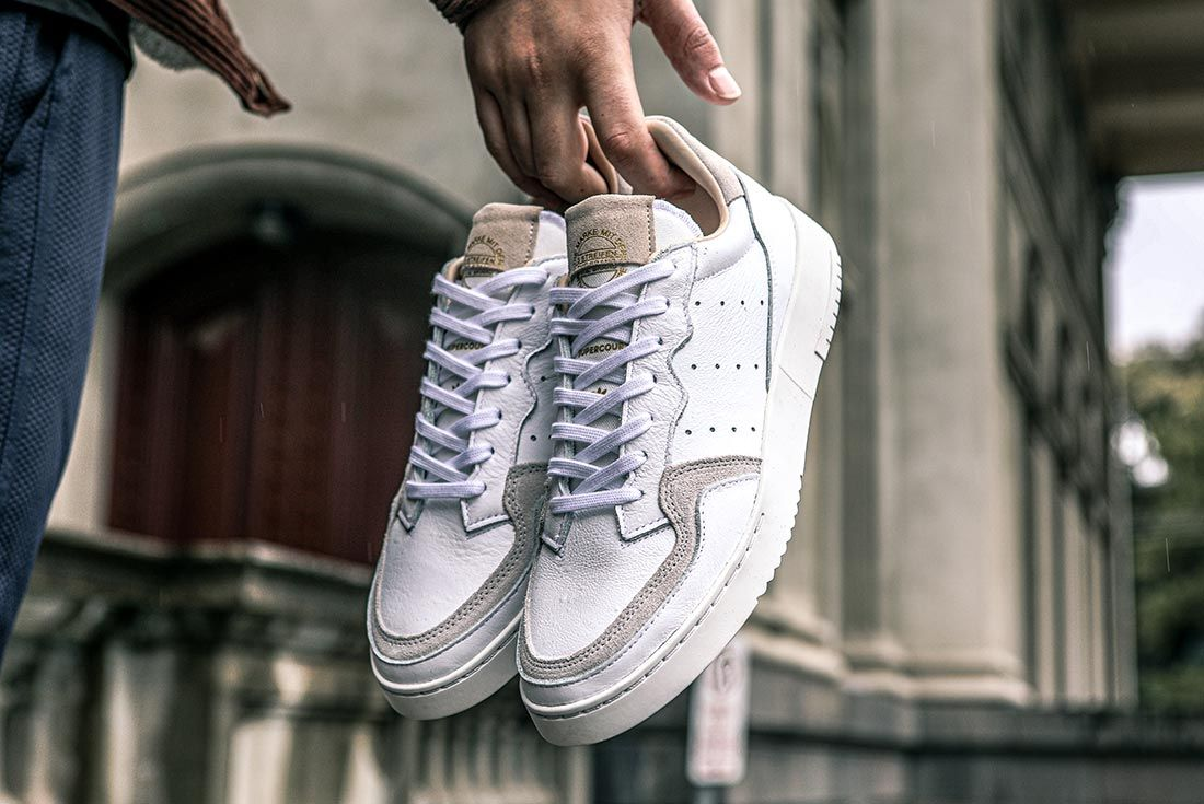 Adidas Supercourt On Foot Holding Shoes