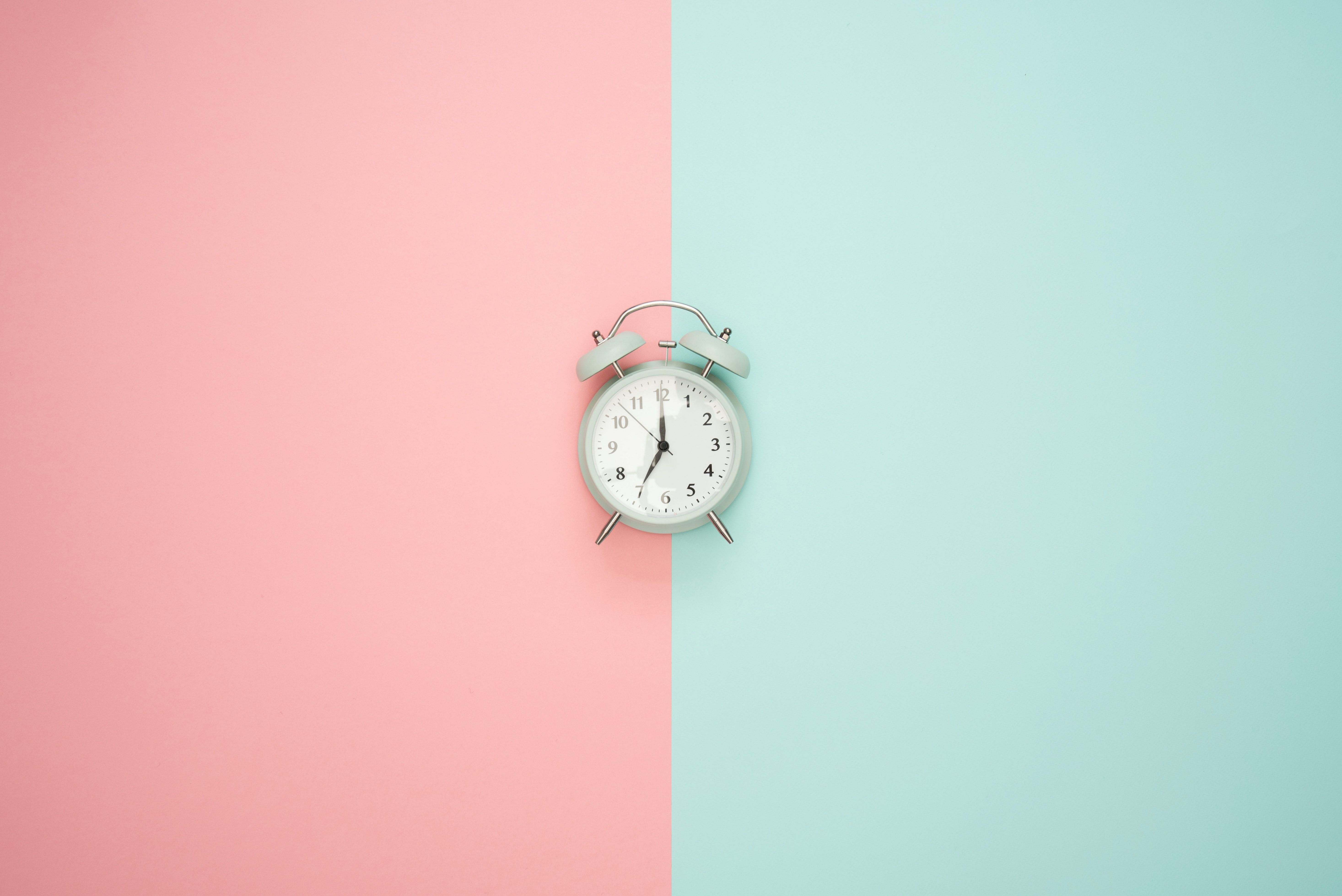 A traditional alarm clock in the center of two colored background