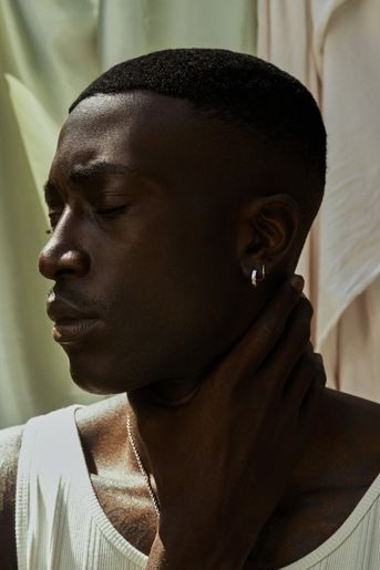 Black man holds his neck, against a serene backdrop