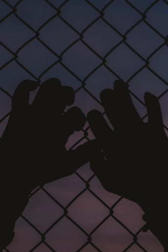 Against purple sky, hands reach up against fence