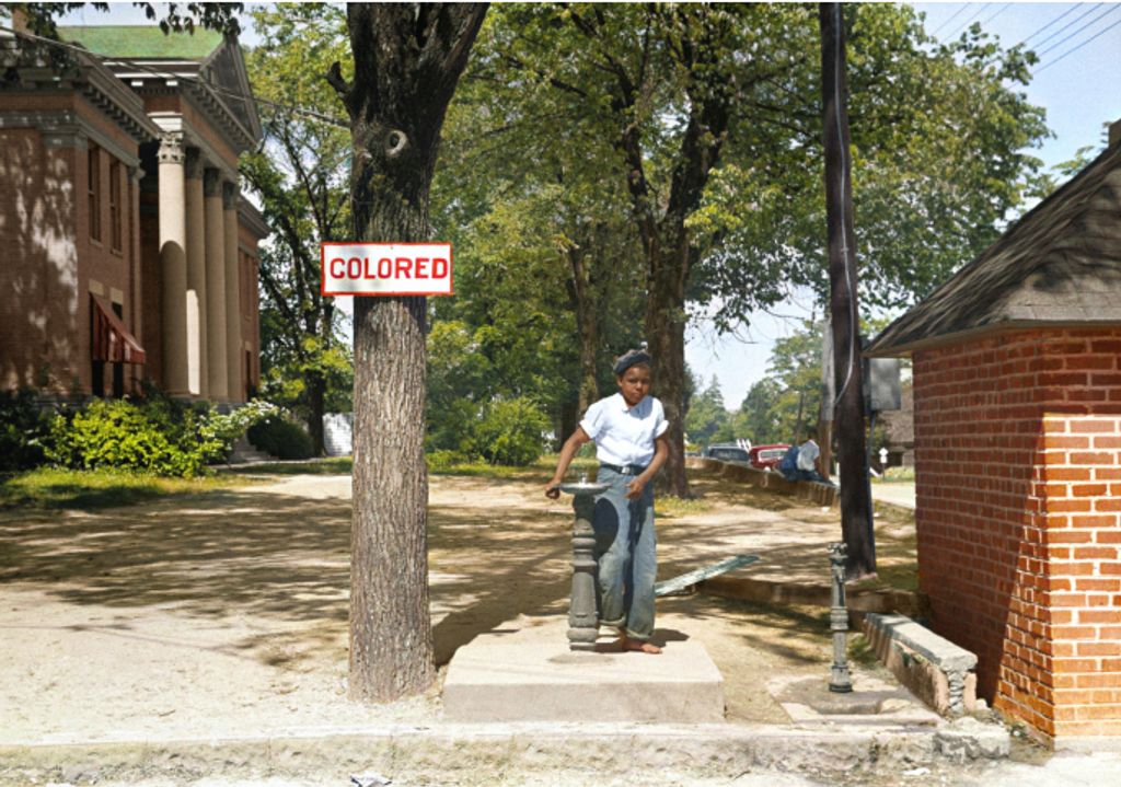 "Young black boy drinking from a fountain on the country courthouse lawn in North Carolina next to a sign that says ""Colored"""