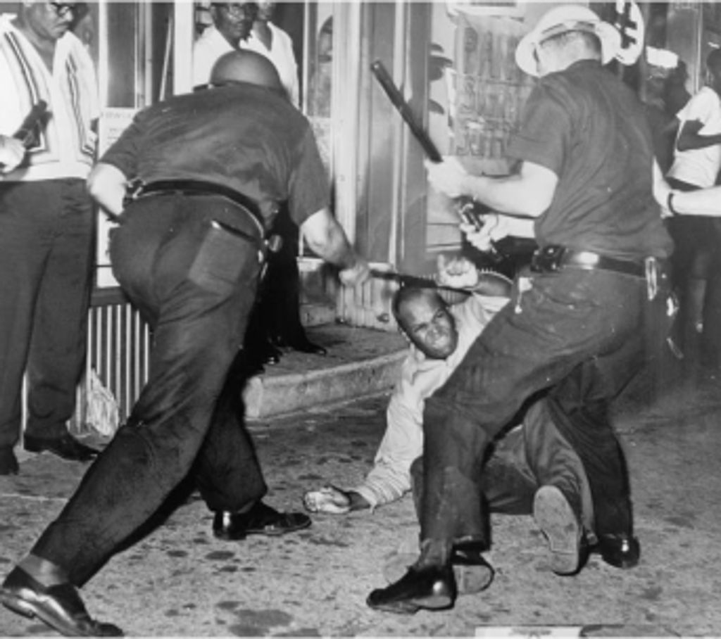 A black and white photograph of two white policemen brutally beating a black man helpless on ground, with batons