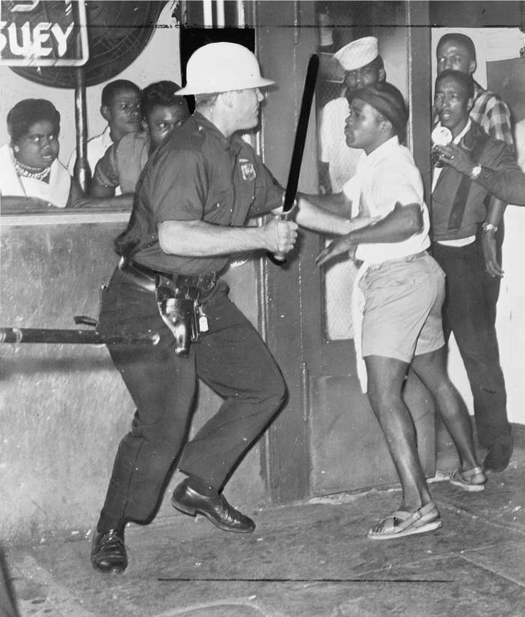 Police officer lifts a police baton at a young black man