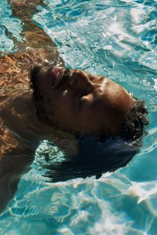 Young black man floating in pool of water peacefully swimming