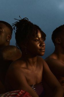 Young black woman sits between two friends at beach, staring into sunset