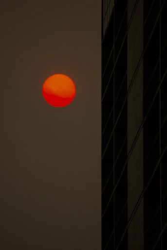 Dark sky with orange red moon next to the side of a cityscape